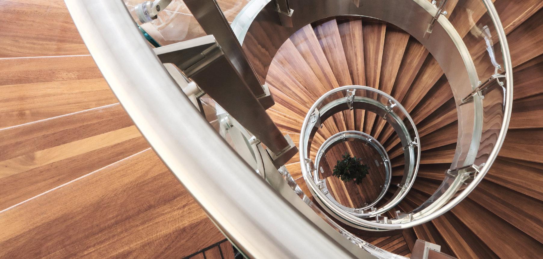 Wendeltreppe mit Stufen aus Holz und einem Edelstahlgeländer